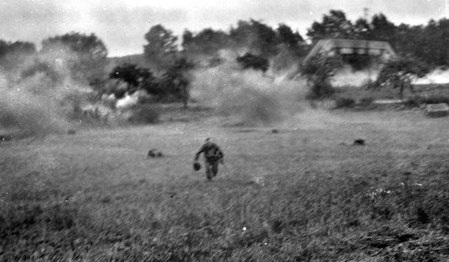 An American runs for cover as artillery and mortar fire lands around him near Dornot, France.