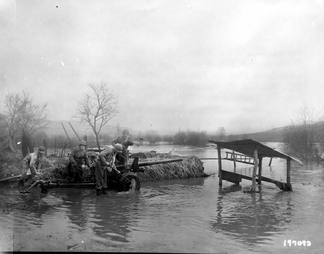 Gun crewmen use the Moselle River to wash the mud off their 57mm antitank weapon. The gun had a muzzle velocity of about 3,000 feet per minute and the antitank round could penetrate two inches of armor plate at 100 yards, but was virtually useless against the thicker frontal armor found on most panzers.