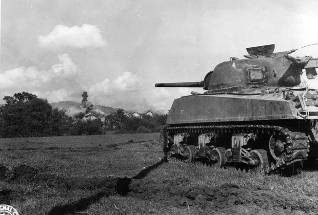 An American M4 Sherman tank provides covering fire as men from the 320th Infantry Regiment, 35th Division, advance near the Marne-Rhine Canal.