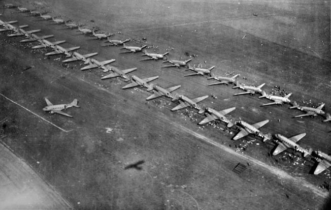 Airborne soldiers can be seen preparing to enter their transport planes at an English airfield. Over 1,100 C-47s delivered some 20,000 U.S., British, and Polish paratroopers during the operation.