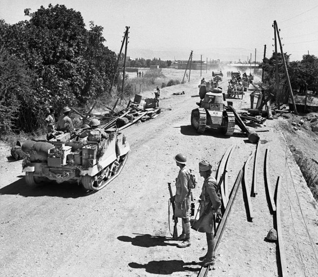 A Bren gun carrier manned by Indian troops heads toward Damascus. A disabled Vichy FT-17 tank lies on the right side of the road.