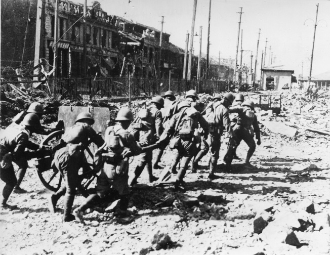 Manhandling an artillery piece, Japanese troops advance toward enemy positions through the ruins of a Chinese city.