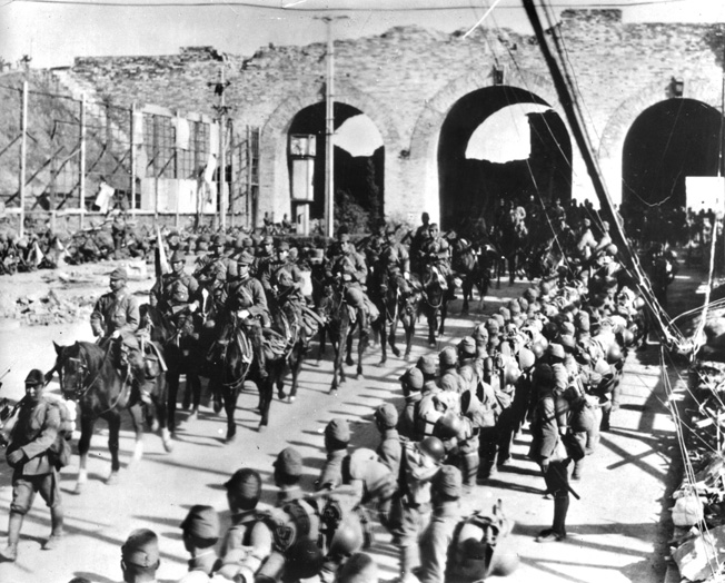 Following a brutal assault, conquering Japanese troops parade triumphantly through the Chungshan gate that leads into Nanking, the capital of China.
