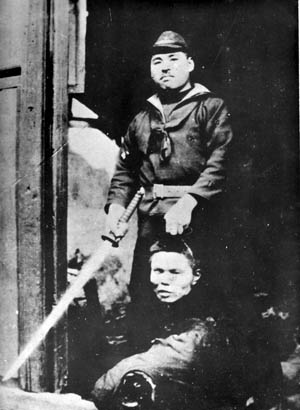 Proudly posing for the camera, a Japanese soldier shows off his grisly trophy.