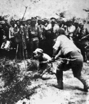 With his men as witnesses, a Japanese officer beheads a Chinese prisoner. Such acts were designed to harden soldiers toward death.