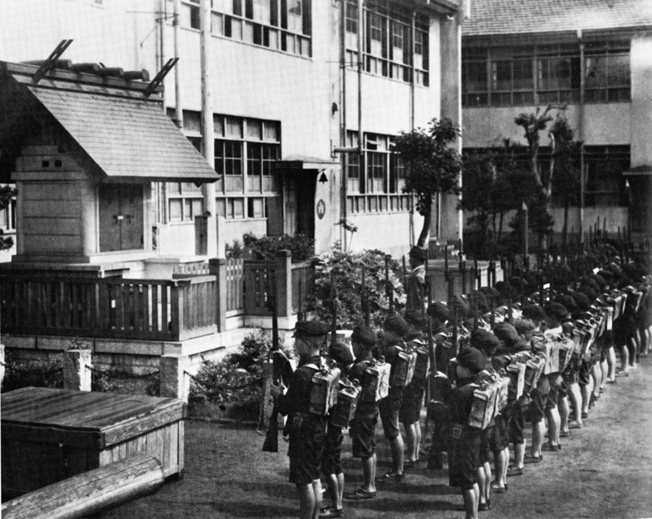 Militarism permeated every aspect of Japanese society. Here, schoolboys dressed in military uniforms and armed with toy weapons salute a picture of the emperor.