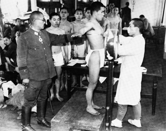 An officer watches as Japanese teenagers are given their pre-induction physicals.