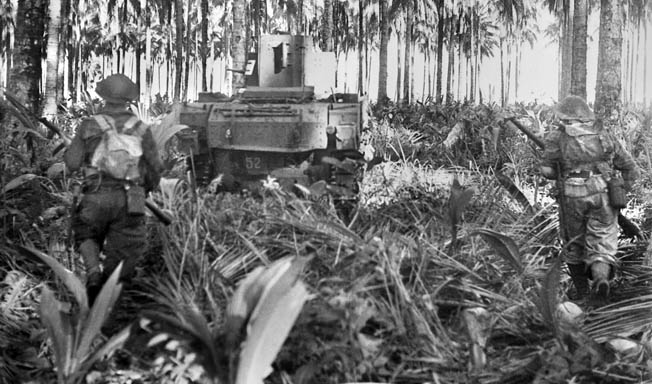 Moving against Japanese defenses during the final assault at Buna, New Guinea, an Australian soldier stays close to the cover of a light tank that is leading the way toward the enemy.