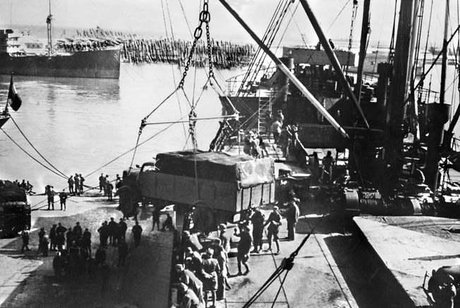 German military vehicles are offloaded from cargo ships at the port of Tripoli, Libya, April 1, 1941. By disrupting the Axis supply line, the Allies gained a matériel advantage over the Germans and Italians in the North African Campaign.