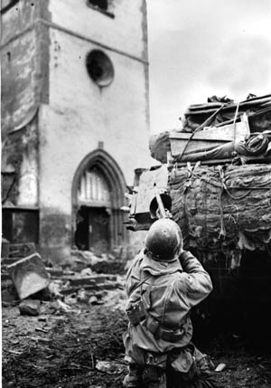Using a tank as a shield, an American GI fires on a German sniper holed up in church in the Alsace village of Oberhoffen-sur-Moder, southeast of Haguenau, France. Brutal winter weather and the difficulty of urban warfare gave the initial advantage to the Germans at the start of Operation Nordwind during the first weeks of 1945.