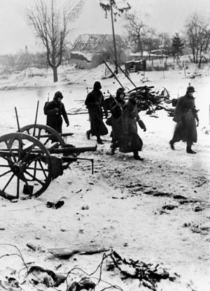 German troops, protected from the bitter cold by their long, heavy greatcoats, move into position during the fighting in the Alsace-Lorraine region, January 1945.