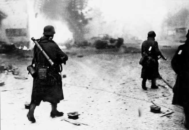 Members of a German grenadier unit pass scenes of fiery destruction during the Alsace fighting.
