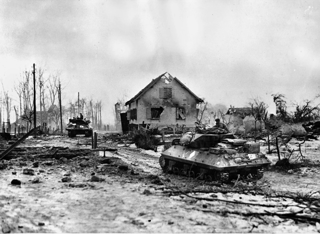 Allied tank destroyers, manned by French troops, rumble through the war-ravaged streets of Bettenhoffen on their way to Gambsheim, seven miles northeast of Strasbourg.