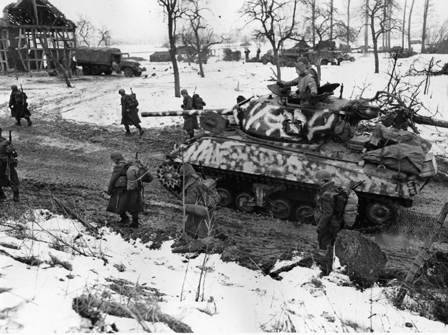 Infantrymen accompany a camouflaged Sherman tank on a snowy, muddy road during the Allied advance on Colmar, France, January 1945.