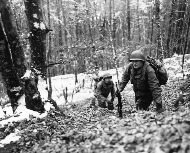 Two soldiers from the U.S. 45th Infantry Division's 1st Battalion, 157th Infantry Regiment, lug rations and supplies through the deep snow to buddies dug in on an Alsace hillside. Resupplying frontline troops was a real challenge for both sides.