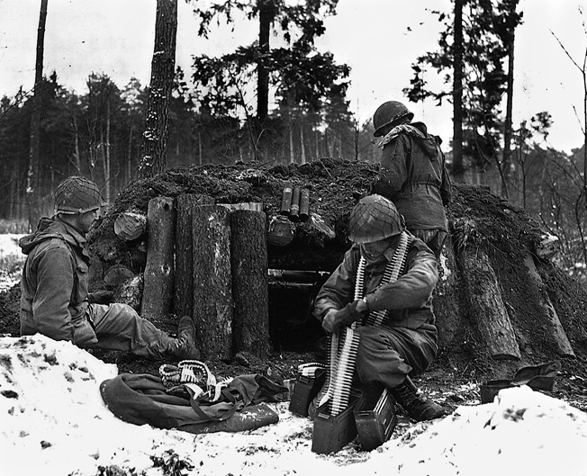 Soldiers of Task Force Linden (Company I, 242nd Regiment, 42nd Infantry Division) prepare for action at their log-and-dirt bunker near Kauffenheim, France, January 8, 1945.