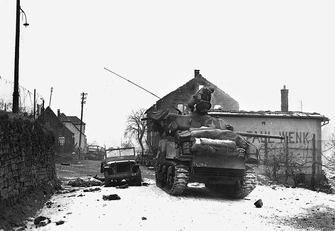 An M-4 Sherman tank of the 781st Tank Battalion stands guard at Wingen-sur-Moder, France. The wrecked jeep, GI helmet, and burning truck in the background attest to the ferocity of the fighting in Alsace.