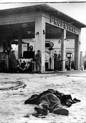 A dead German soldier lies on a snow-covered street in Colmar as Allied forces fight their way into the Alsatian city on February 2, 1945. Allied infantrymen stand near antitank guns set up in a gasoline station.