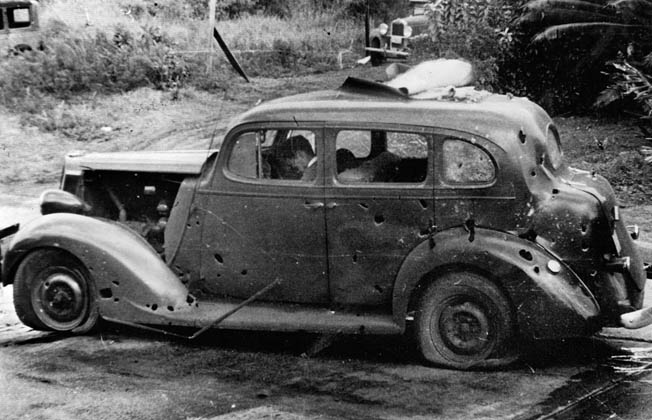 Three civilians lie dead in their car after it was hit by fragments from falling antiaircraft munitions.