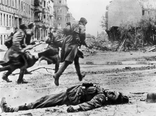 A Berlin defender lies dead as Soviet soldiers rush into the heart of the city, May 1945. With their men either dead, captured, or gone, German women were vulnerable to the rampaging Soviets.