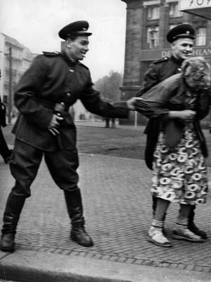 After the war's end, a pair of smiling, well-dressed Soviet soldiers accost a German woman on a street in