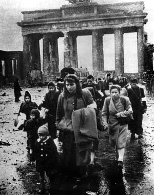 With fear on their faces, a line of German woman and children rush past the battered Brandenburg Gate, hoping to escape the Soviet occupiers.