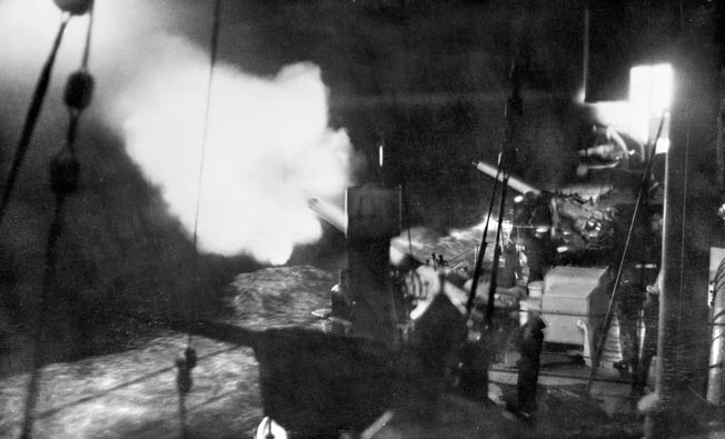 The guns of the Australian cruiser Canberra fire a salvo during a night exercise. During the Battle of Savo Island the cruiser was able to fire only a few rounds before it was so severely damaged that it could no longer participate in the fighting.