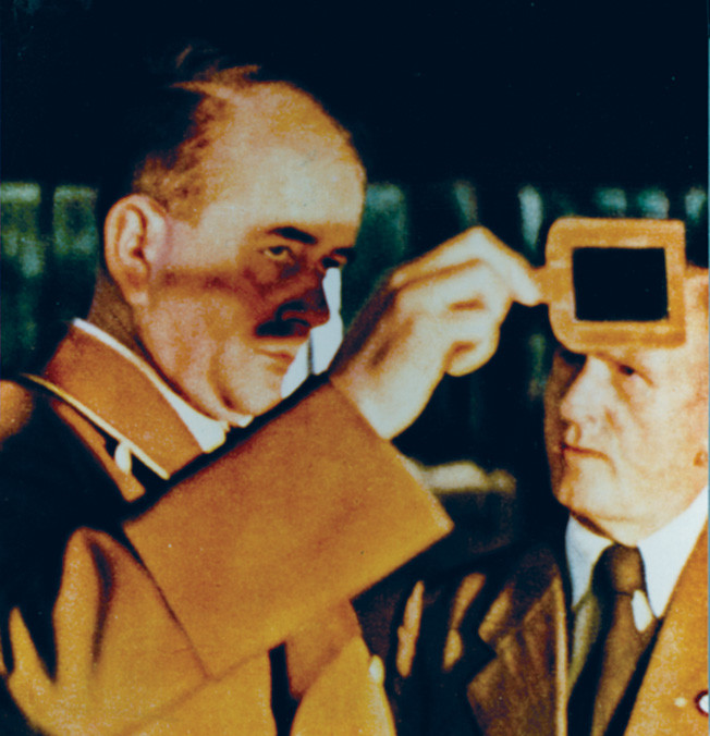 Speer protects his eyes while inspecting the process of pouring molten steel in his role  as German minister of armaments and war production.