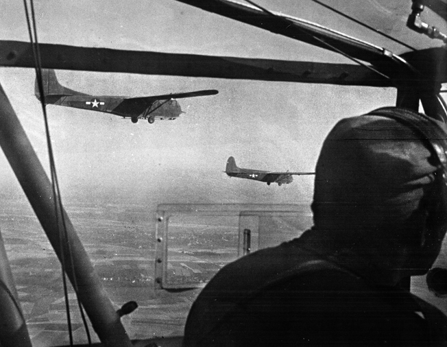Two CG-4A Waco gliders, being towed by a single C-47, approach the release point near Wesel. Each Waco could carry 13 soldiers, a 75mm howitzer, a jeep, or a 1/4-ton trailer; 906 American gliders took part in Varsity.