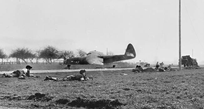 With a British Horsa glider lying in the background, 17th Airborne Division troops stay low while enemy machine-gun fire sweeps the ground near Wesel.