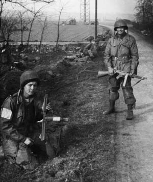 While soldiers behind them guard a road junction near Wesel, Goldie Goldman (left) and Don Manke pose with their tommy guns for Warner's camera. Both survived the war.