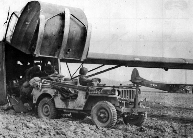A jeep exits a CG-4A through the hinged nose fitted with Corey skids. Warner's glider carried a jeep that had to be abandoned on the landing zone due to intense German fire.