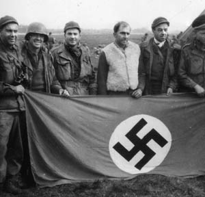 """The spoils of war. Flight Officer Tom Warner (third from left) and some buddies pose with a captured Nazi flag """"somewhere in Germany."""""""