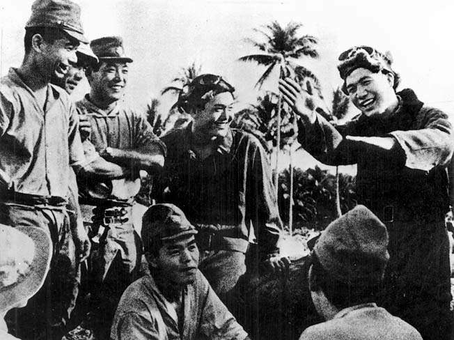 A happy Japanese pilot (right) demonstrates to his comrades some of the aerial combat moves he made against the Marine aviators.