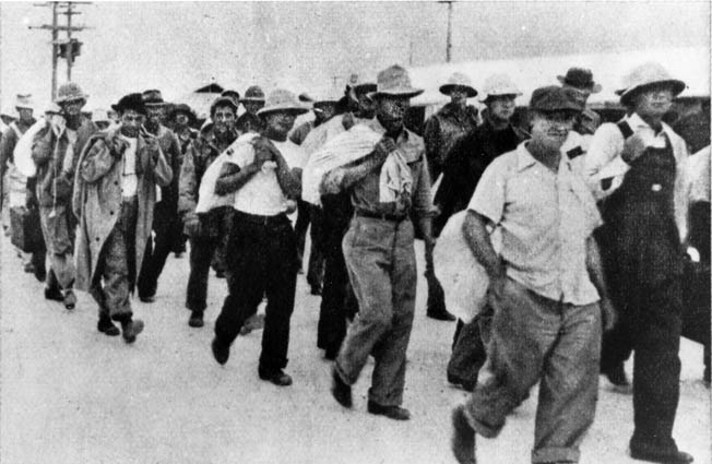 Civilian contractors are marched off to captivity after Wake fell to the Japanese, December 23, 1941. Some contractors remained to finish construction projects under Japanese occupation. Fearing a fifth-column uprising, the Japanese executed 98 contractors in October 1943—an atrocity for which the atoll commander, Rear Admiral Shigematsu Sakaibara, was hanged after the war.