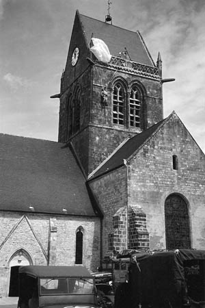 A dummy representing Private John Steele, F Company, 505th PIR, 82nd Airborne Division, still hangs from the steeple of the church in Sainte-Mère-Église. In actuality, Steele hung from the opposite side of the steeple.