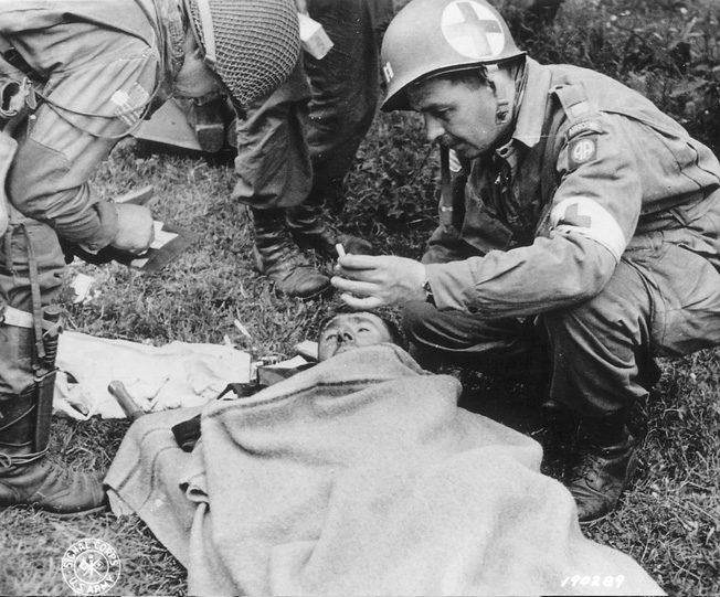 A captain in an 82nd Airborne Division medical unit (right) gives a cigarette to a wounded German soldier.