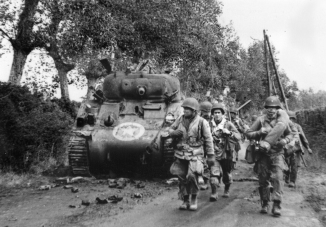 A unit of 82nd Airborne Division troopers advances past a knocked-out M4 Sherman tank along a hedgerow in Normandy.