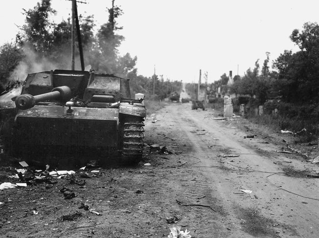 A destroyed German self-propelled gun smolders along the road leading from Neuville-au-Plain to Sainte-Mère-Église. Private John E. Atchley, H Company, 505th PIR, was credited with destroying the assault gun with a 57mm antitank gun—the first time he had ever fired one.  His courageous stand caused the Germans to halt their armored counter-attack against Sainte-Mère-Église.