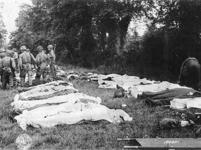 Dead American paratroopers are gathered in a field by a Graves Registration unit prior to burial.