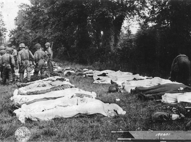 Dead American paratroopers gathered in a field by a Graves Registration unit prior to burial.