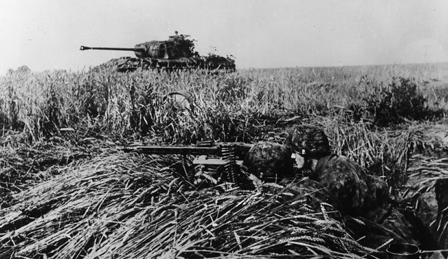 The Germans await: a pair of SS panzer-grenadiers, supported by a Panther medium tank, man their MG-42 machine gun in a field near Caen, July 1944.