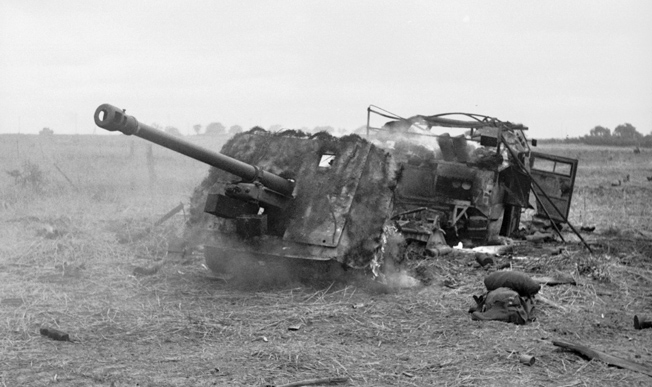 A British 17-pounder antitank gun and Morris C8 Quad artillery tractor knocked out and burning after the battle for Hill 112, July 15.