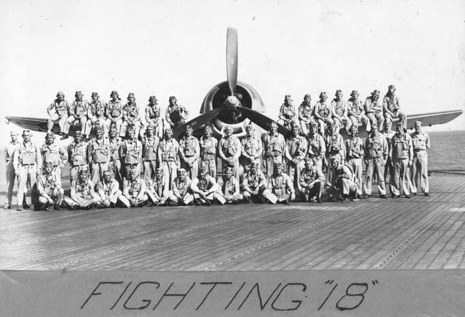The pilots of Crosby's Squadron VF-18 photographed with a U.S. Navy Grumman Hellcat on the flight deck of the USS Bunker Hill (CV-17).