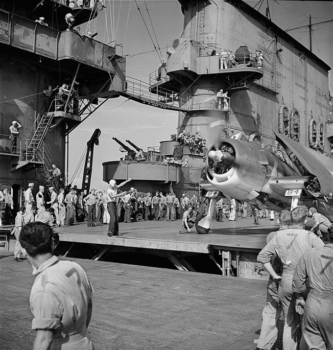 A carrier's flight-deck crew watches carefully as an officer guides a Hellcat toward the elevator, which is being raised into position, November 1943. Each plane was assigned a captain who was responsible for staying with that particular plane. Pilots, however, did not fly the same plane.