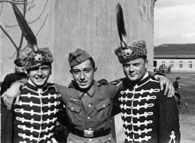 """Two soldiers have been """"volunteered"""" to serve as extras in one of Josef Goebbels's epic historical propaganda films. Some 2,000 were produced during the Third Reich's 12 years and literally to the very last days of the war. While the actors wear plumed caps, their standard-issue comrade wears an M34 field cap that was nicknamed  Schiffschen or """"little boat"""" because of its shape."""