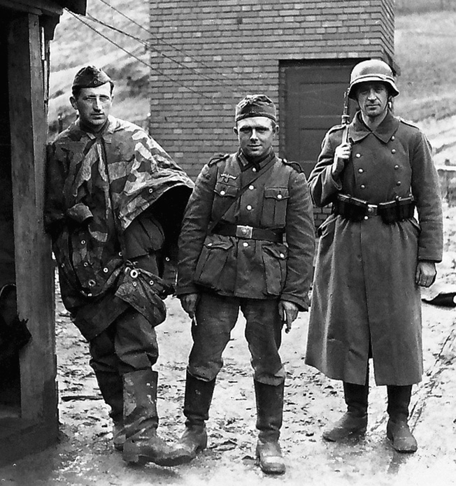"""Models—Standard Army Issue (Above) As if posing for a catalogue photo, three soldiers in a casual photo happen to display three variations of Army uniforms and equipment. The soldier on the left wears the """"all-purpose"""" Zeltbahn (1934 camouflage pattern in green, brown, and beige). The triangular-shaped item could be worn as a poncho, for concealment or several could be lashed together to create a makeshift shelter.  The enlisted man or Landser in the center wears the standard-issue infantry uniform used in the Polish and French campaigns with relatively little change from the WWI German uniform (including the Model 1911 triple rifle cartridge pouches). The gray-green M35 tunic is matched to basic field-gray trousers. It features the national emblem of eagle and swastika on the right, standard for all ranks.  The third trooper wears the field-gray long winter coat or Ubermantel and what appears to be an M35 steel helmet while his companions wear soft field caps. All three are shod in the standard marching boots (Marschstiefel) produced up to 1940, when shorter lace-up boots were introduced to save costs and leather.  The so-called """"jackboots,"""" nicknamed Knobelbecher or """"dice-shakers,"""" featured the well-known hobnail-impregnated soles. The soldiers also wear the standard enlisted man's silver metal belt buckle with the inscription """"Gott Mit Uns"""" —""""God with us."""""""