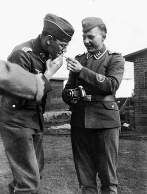 """A color photo would reveal that these uniforms were of a light blue color while the patch on the cameraman indicates he is a member of a geographical mapping unit. The three """"wings"""" on both men's collar tabs indicate a rank of Obergefreiter (corporal) while their smoking comrade is an NCO Stabsfeldwebel (staff sergeant)."""