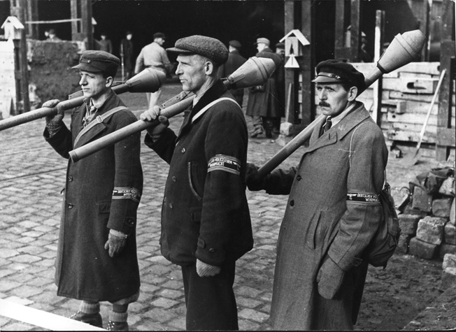 With dour expressions, three middle-aged militia members carry panzerfausts, which required little skill to operate, and wear Volkssturm armbands. Unable to provide all VS troops with uniforms, the German high command trusted that the armbands would be enough to identify the wearer as a regular military combatant and not a partisan.