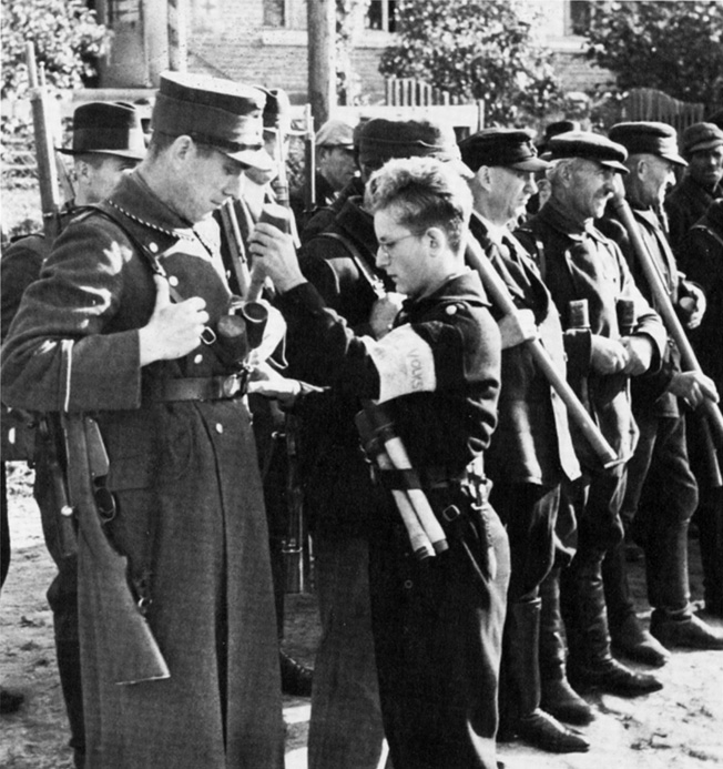 A teenage member of the Hitler Youth distributes grenades to a motley group of Volkssturm troops. Some men carry panzerfaust antitank wepons, others outdated rifles.
